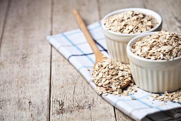 Flocons d'avoine dans des bols en céramique et une cuillère en bois sur une serviette en lin, oreilles de blé dorées