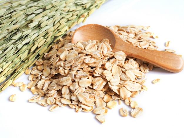 Flocons d'avoine dans une cuillère en bois avec des grains secs et une oreille de riz