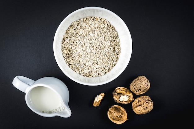 Flocons d'avoine dans une tasse et noix ailées et lait. recette de flocons d'avoine aux noix, pruneaux, cannelle et sucre.