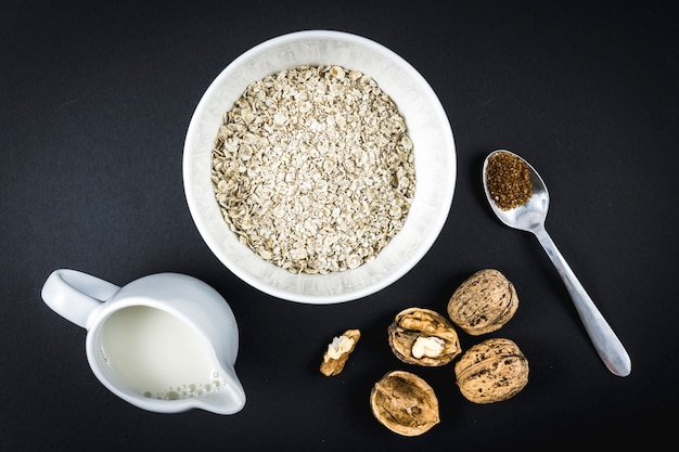 Flocons d'avoine dans une tasse et noix ailées, lait et sucre. recette de flocons d'avoine aux noix, pruneaux, cannelle et sucre.