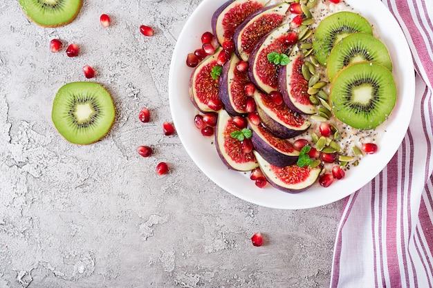 Flocons d'avoine délicieux et sains avec des figues, du kiwi et de la grenade. petit-déjeuner sain. nourriture de fitness. nutrition adéquat. mise à plat. vue de dessus.
