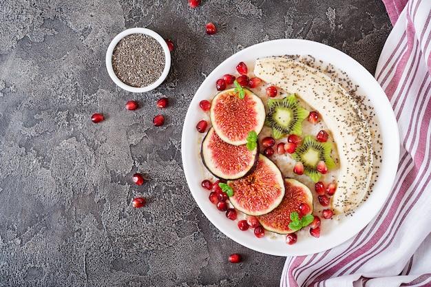 Flocons d'avoine délicieux et sains avec des figues, des kiwis, des grenades, des bananes et des graines de chia. petit-déjeuner sain. nourriture de fitness. nutrition adéquat. mise à plat. vue de dessus.