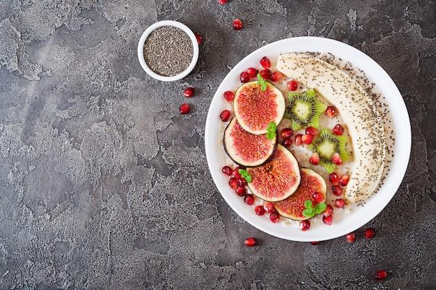 Flocons d'avoine délicieux et sains avec des figues, des kiwis, des grenades, des bananes et des graines de chia. petit-déjeuner sain. nutrition adéquat. mise à plat. vue de dessus.
