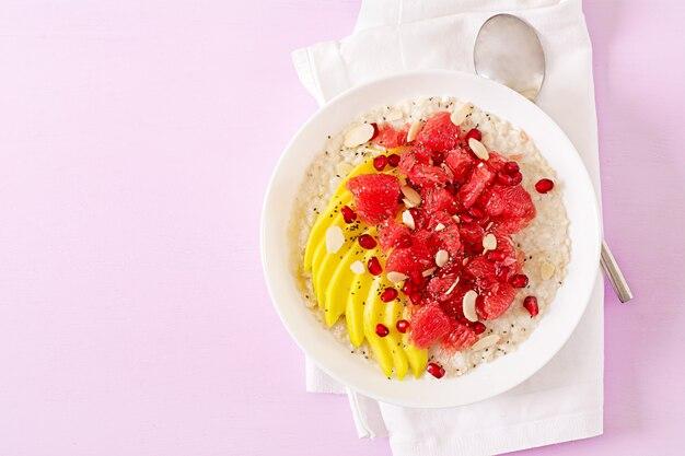 Flocons d'avoine délicieux et sains avec des pamplemousses, des grenades, des amandes et des graines de chia. petit-déjeuner sain. nourriture de fitness. nutrition adéquat. mise à plat. vue de dessus.