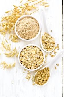 Flocons d'avoine et farine dans des bols, grain dans une cuillère, tiges mûres d'avoine sur fond de planche de bois d'en haut