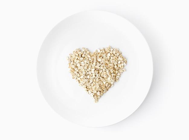 Flocons d'avoine en forme de coeur tiré d'en haut sur une plaque blanche sur fond blanc alimentation biologique végétarienne. espace pour le texte. vue de dessus. mise à plat.