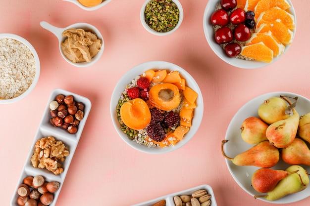 Flocons d'avoine avec fruits, noix, beurre d'arachide dans des bols
