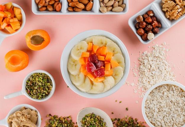 Flocons d'avoine avec fruits, noix, beurre d'arachide, flocons d'avoine dans un bol