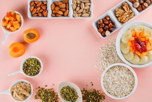 Flocons d'avoine avec fruits, noix, flocons d'avoine, beurre d'arachide dans un bol