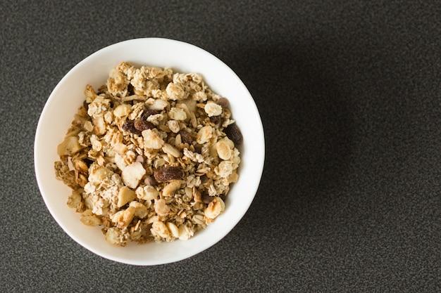 Flocons d'avoine ou granola aux noix, fruits secs et baies sur table en pierre noire.