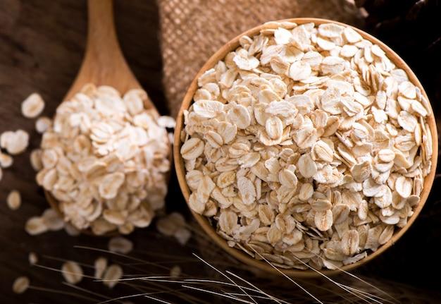 Flocons d'avoine roulés dans une cuillère en bois et un bol.