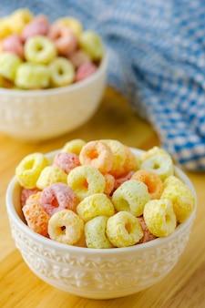 Flocons de céréales dans un bol blanc avec espace copie, concept de petit-déjeuner. nourriture avec un délicieux goût fruité et des couleurs fruitées
