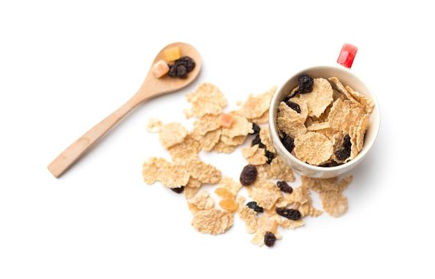 Flocons de céréales à grains entiers qui mélangent des petits fruits et des raisins secs pour le petit déjeuner isolés sur un espace blanc