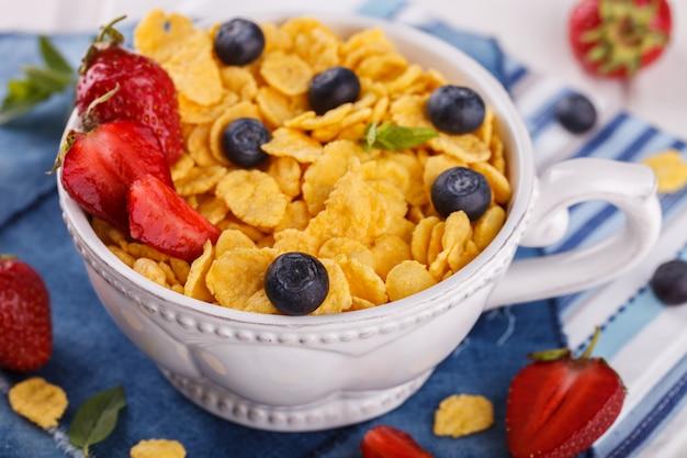 Flocons de maïs et baies fraîches. petit-déjeuner équilibré pour l'été.