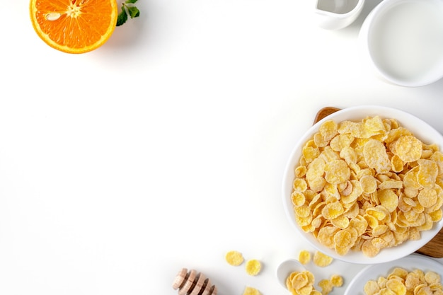 Flocons de maïs bol bonbons avec du lait et orange sur fond blanc, gros plan, concept de design de petit déjeuner frais et sain.