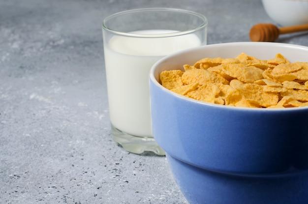 Flocons de maïs dans une assiette et lait dans un verre. petit-déjeuner sain. espace copie