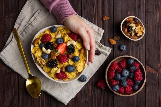 Flocons de maïs dans un bol avec des baies et une main féminine sur fond de bois. vue de dessus du petit déjeuner sain.
