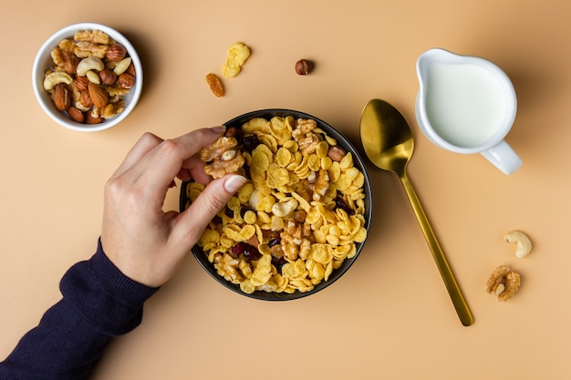 Flocons de maïs dans un bol avec des écrous tenus par des mains féminines sur fond jaune. vue de dessus du petit déjeuner sain.