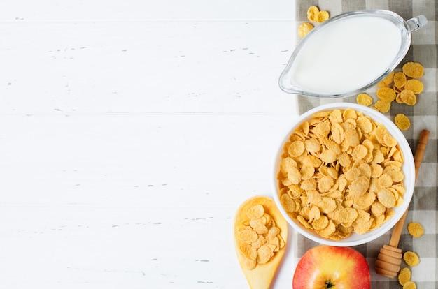 Flocons de maïs, lait et pomme sur la nappe. petit déjeuner sain et nutritif. fond blanc. espace copie