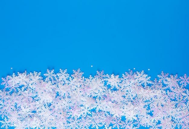 Flocons de neige artificiels blancs sur fond bleu doux. fond d'hiver. modèle décoratif pour cartes, bannière, affiche.