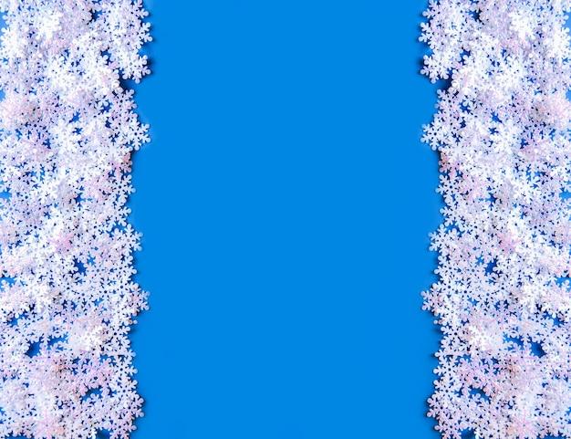Flocons de neige artificiels blancs sur fond bleu doux. fond symétrique d'hiver. modèle décoratif pour cartes, bannière, affiche.