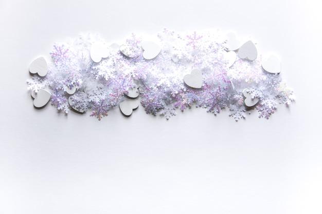 Flocons de neige artificiels blancs sur fond clair doux. fond d'hiver. modèle décoratif pour cartes, bannière, affiche.