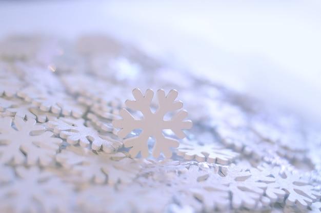 Flocons de neige artificiels blancs sur fond doux. fond d'hiver. modèle décoratif pour cartes, bannières, affiches.