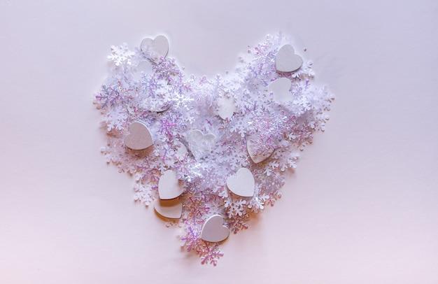 Flocons de neige artificiels blancs en forme de coeur sur fond de lumière douce. fond d'hiver. modèle décoratif pour cartes, bannière, affiche.