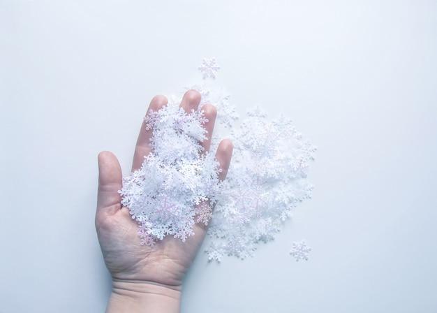 Flocons de neige artificiels blancs à la main sur fond de lumière douce. fond d'hiver. modèle décoratif pour cartes, bannière, affiche.