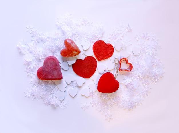 Flocons de neige artificiels et coeurs décoratifs rouges sur fond blanc doux.