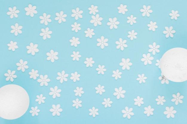 Flocons de neige blancs et boule de noël sur un fond bleu doux