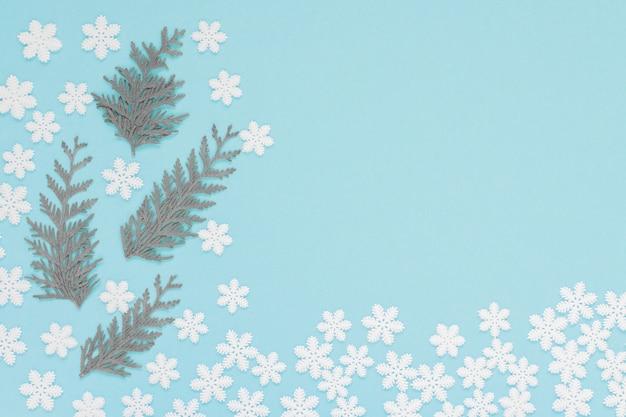 Flocons de neige blancs et brindilles de thuya sur fond bleu doux