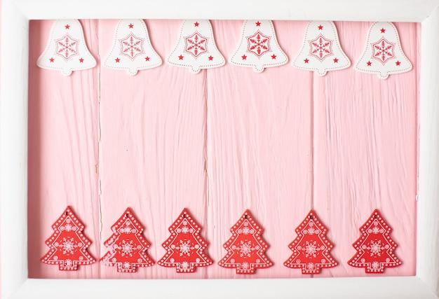Flocons de neige blancs et rouges, cloches et arbre de noël sur une surface en bois rose