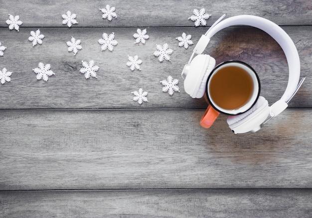 Flocons de neige près des écouteurs et du thé