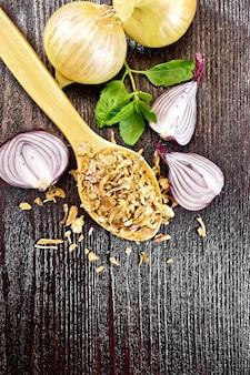 Flocons d'oignons séchés dans une cuillère, oignons violets et jaunes, basilic sur fond de planche de bois d'en haut