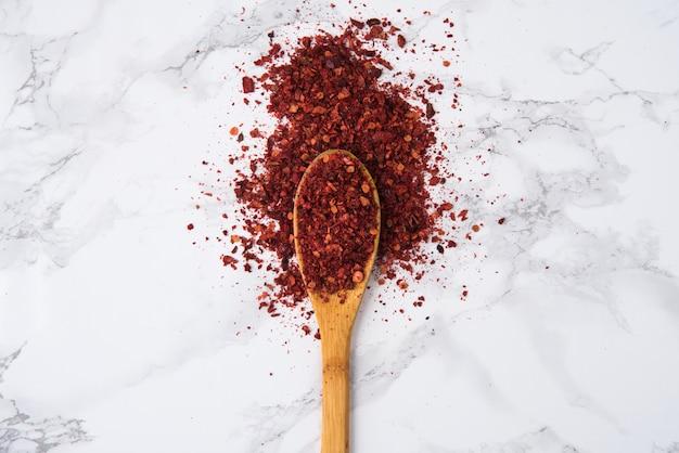 Flocons de piment rouge chaud dans une cuillère en bois