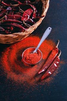 Des flocons de piment rouge et de la poudre de chili éclatent sur fond noir