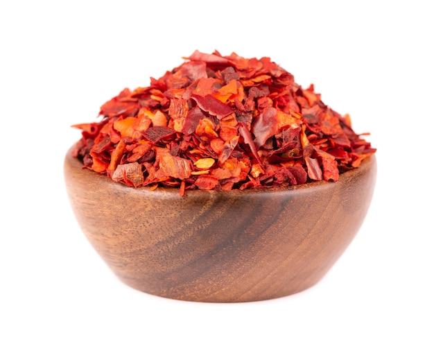 Flocons de piment rouge séché dans un bol en bois, isolé sur fond blanc. piment de cayenne haché. épices et herbes.