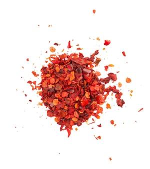 Flocons de piment rouge séché avec des graines, isolés sur fond blanc. piment de cayenne haché. épices et herbes. vue de dessus.