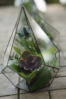 Florarium avec des fleurs fraîches et succulentes. event décoration de fleurs fraîches. flux de travail du fleuriste. repas de noces
