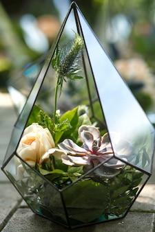 Florarium avec des fleurs fraîches succulentes et roses