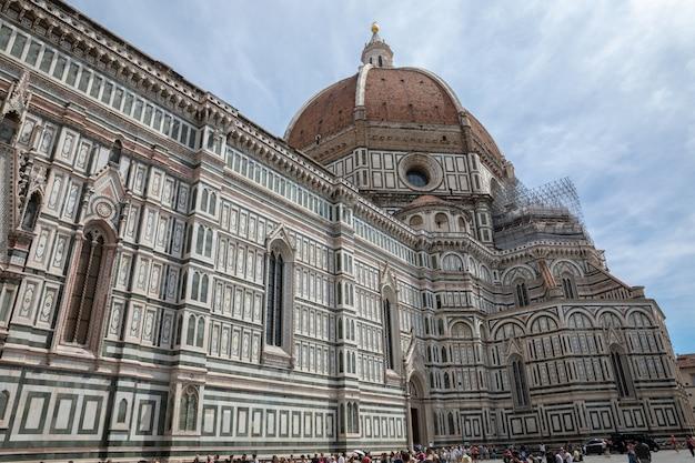 Florence, italie - 24 juin 2018 : vue panoramique sur la cattedrale di santa maria del fiore (cathédrale de sainte marie de la fleur) et le campanile de giotto. les gens marchent sur la place en été