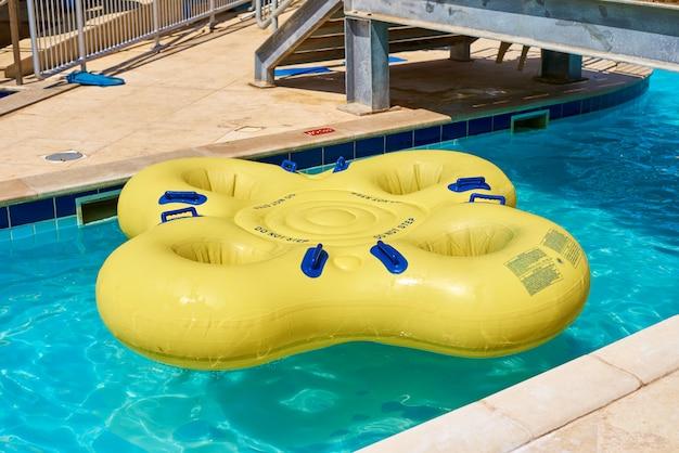 Flotteur gonflable jaune dans la piscine bleue dans le parc aquatique