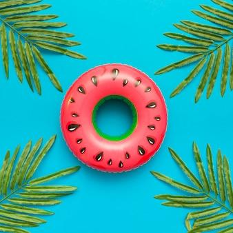 Flotteur de piscine de melon d'eau avec des palmiers de feuilles tropicales