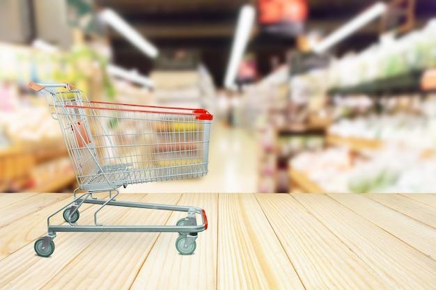Flou abstrait allée de fruits et légumes frais biologiques sur les étagères des épiceries sur fond de magasin de supermarché avec panier et table en bois