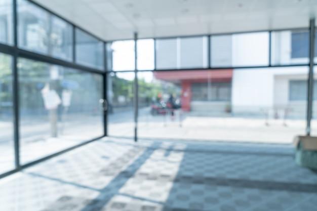 Flou abstrait bureau vide avec fenêtre en verre et lumière du soleil pour le fond