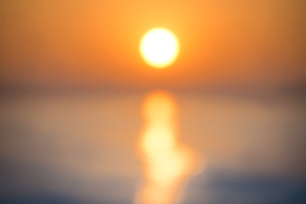 Flou abstrait coucher de soleil sur la mer avec soleil, vagues et lumière brillante sur l'arrière-plan flou d'eau