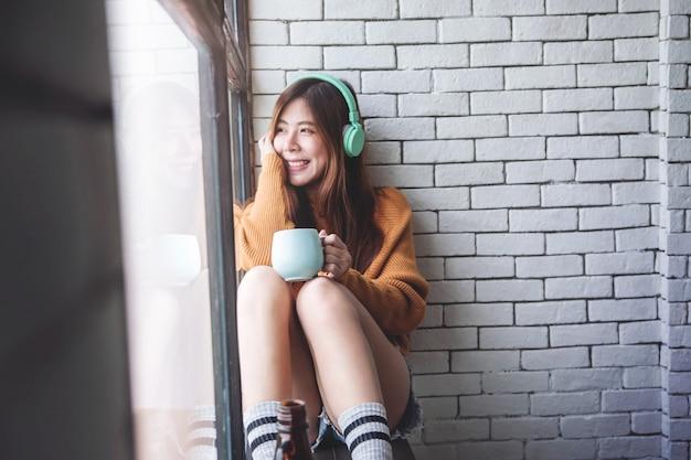 Flou artistique de la jeune femme se détendre avec de la musique de casque dans une maison confortable