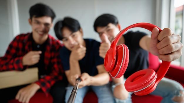 Flou artistique de jeunes blogueurs masculins démontrant un casque rouge à l'appareil photo tout en filmant une vidéo pour un vlog technologique