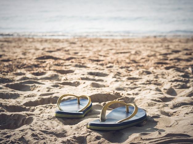 Flou artistique sur une paire de tongs sur la plage de sable blanc